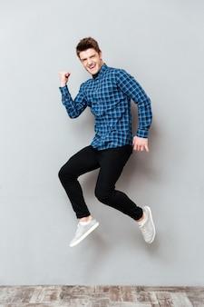 Schreiender junger mann, der über graue wand steht und springt.