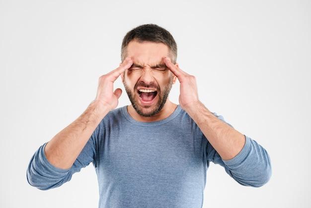 Schreiender junger mann mit kopfschmerzen