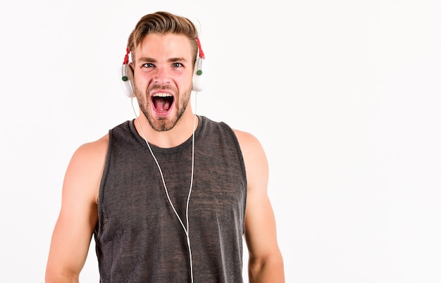 Schreiender kerl. rockmusik. neue technologie im modernen leben. sexy muskulöser mann hört musik. mann hört neues lied isoliert auf weiss. unrasierter mann in bluetooth-kopfhörern. modernes lebenskonzept.