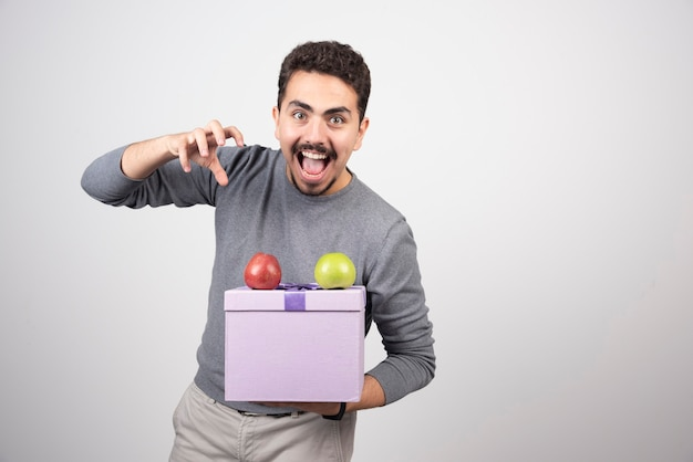 Schreiender mann, der eine lila schachtel mit äpfeln hält.