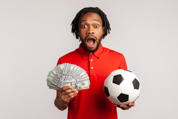 Schreiender mann, der fußball und hundert-dollar-banknoten hält, kamera schaut, wetten und gewinnt.