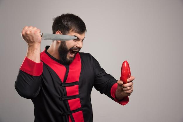 Schreiender mann, der versucht, einen roten pfeffer zu schneiden.