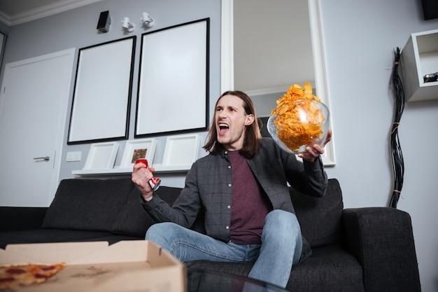 Schreiender mann, der zu hause drinnen sitzt und chips isst