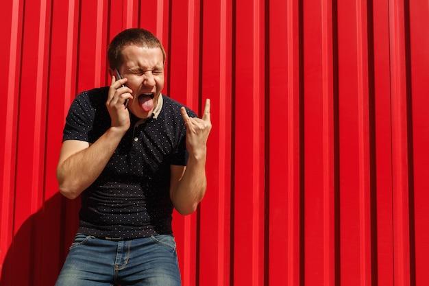 Schreiender mann mit verrückten gefühlen, der sein handy auf rot benutzt