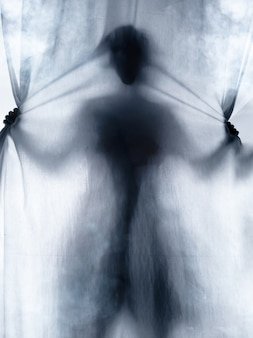Schreiender mensch, der durch stoffvorhang als horrorhintergrund drückt