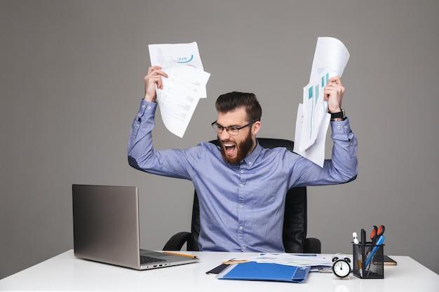 Schreiender unzufriedener bärtiger eleganter mann mit brille, der dokumente hält, während er im büro am tisch sitzt
