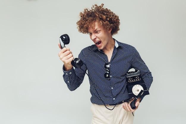 Schreiender wütender retro-mann mit telefon in den händen.