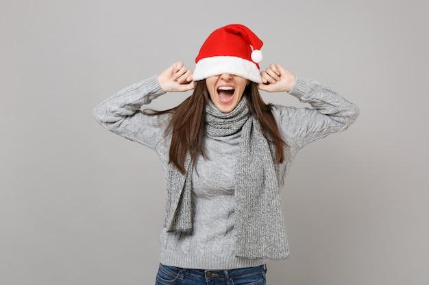 Schreiendes junges weihnachtsmädchen im grauen pulloverschal, der die augen mit weihnachtsmütze bedeckt, einzeln auf grauem wandhintergrund im studio. frohes neues jahr 2019 feier urlaub party konzept. kopieren sie platz.