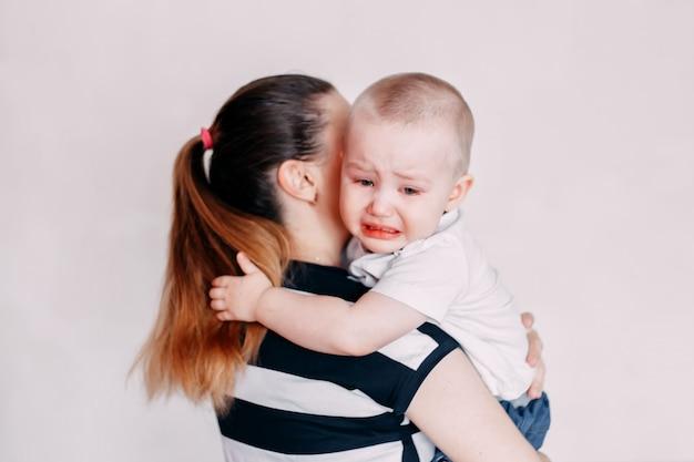 Schreiendes kleinkindmädchen, das von ihrer mutter getröstet wird