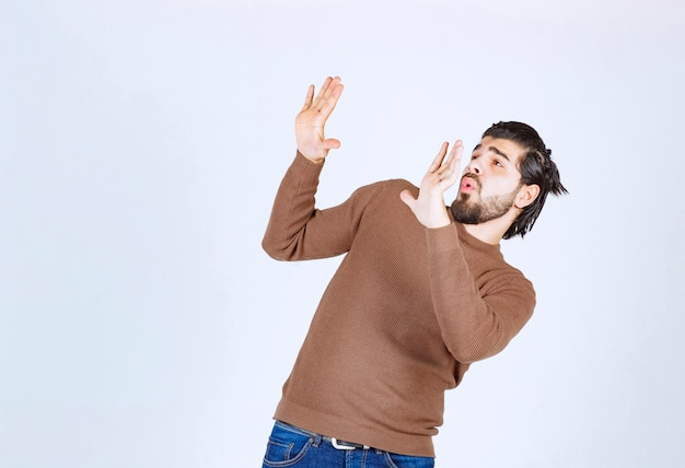 Schreiendes modell des jungen mannes, das unsichtbare wand drückt