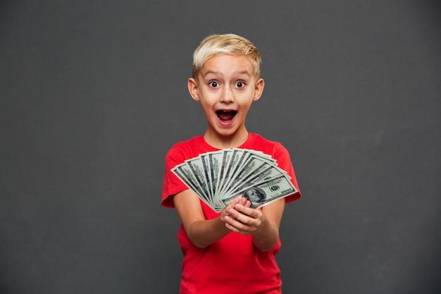 Schreiendes überraschtes kind des kleinen jungen, das geld zeigt.