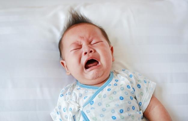 Schreiendes und schreiendes säuglingsbaby, das auf bett liegt