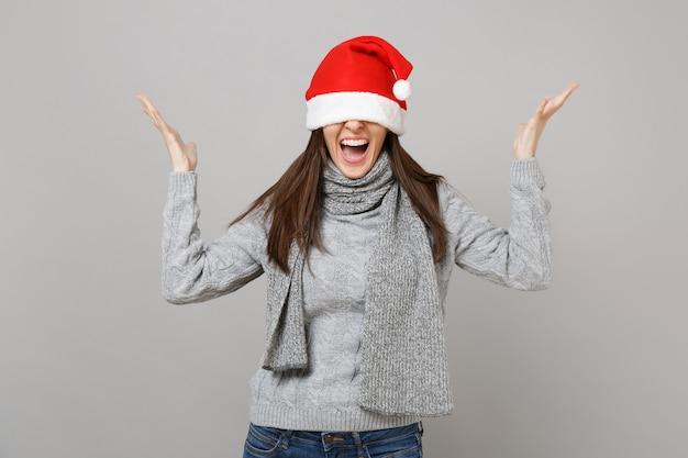 Schreiendes weihnachtsmädchen in grauem pulloverschal, der die augen mit weihnachtsmütze bedeckt, die hände einzeln auf grauem wandhintergrund ausbreitet. frohes neues jahr 2019 feier urlaub party konzept. kopieren sie platz.