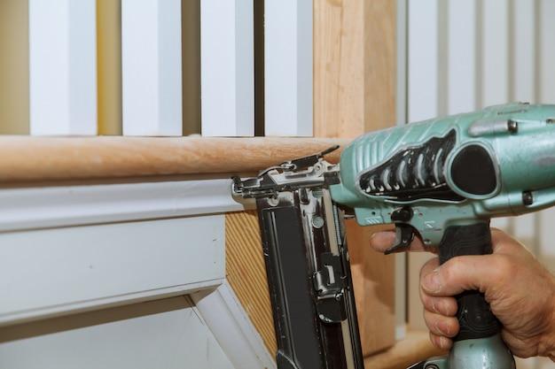 Schreiner-brad mit nagelpistole zum formen von beschichtungen, mit dem warnschild, dass alle elektrowerkzeuge
