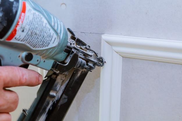 Schreinerei-brad, der nagelpistole verwendet, um ordnung zu ordnen, mit der warnung, die elektrowerkzeuge