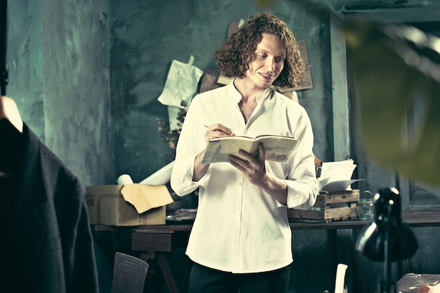 Schriftsteller bei der arbeit. hübscher junger schriftsteller, der in der nähe des tisches steht und sich etwas einfallen lässt