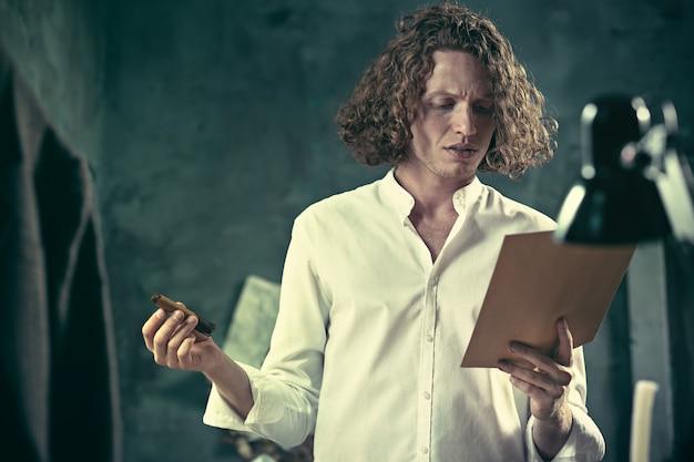 Schriftsteller bei der arbeit. hübscher junger schriftsteller, der in der nähe des tisches steht und sich zu hause etwas einfallen lässt