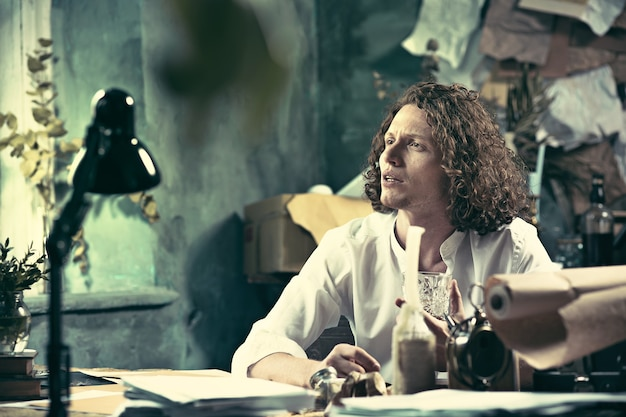 Schriftsteller bei der arbeit. junger schriftsteller, der am tisch sitzt und zu hause etwas in seinen skizzenblock schreibt