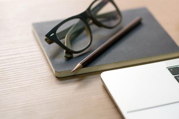 Schriftstellerkarriere auf dem schreibtisch mit weißen kaffeetassen, notizbüchern, bleistiften, gläsern