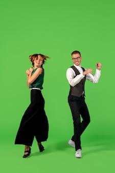 Schritt. altmodische junge frau tanzen auf grünem studiohintergrund isoliert. künstlermode, bewegungs- und aktionskonzept, jugendkultur, moderückkehr. junger stilvoller mann und frau.