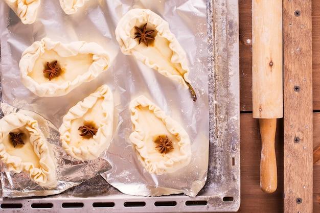 Schritt der herstellung von gebackenen birnen im gebäck. bereiten sie für das backen der birnen auf metallischem backblech vor