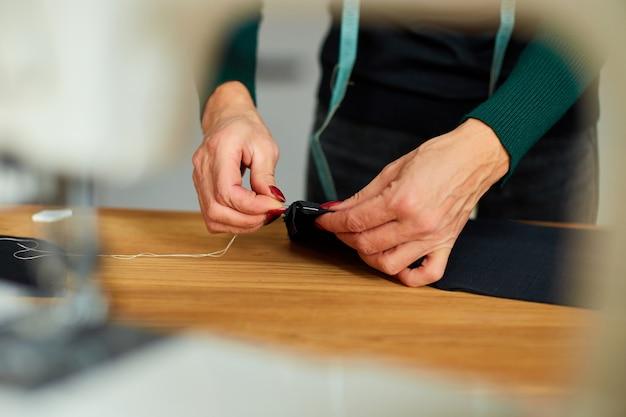 Schritt für schritt, 50-jährige frau, die stoff mit der hand näht, reifer schneider, der mit dem nähen im atelier, in der textilindustrie, im hobby, im arbeitsbereich arbeitet.