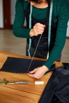 Schritt für schritt, 50-jährige frau, die stoff mit der hand näht, reifer schneider, der mit nähen in atelier, textilindustrie, hobby, arbeitsbereich arbeitet. erstellungsprozess diy, arbeitsplatz der näherin.