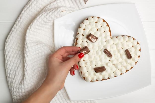 Schritt-für-schritt-anleitung für herzförmige kuchenrezepte. den kuchen mit schokoladenstückchen, waffeln und keksen dekorieren. flach liegen.