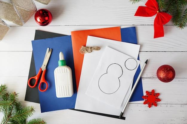 Schritt-für-schritt-fotoanweisung der weihnachtsgirlande mit schneemann. handgemacht für kinder