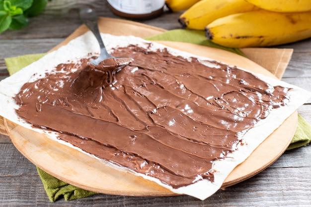 Schritt für schritt leckere brötchen mit bananenscheiben auf holztisch kochen. bananenrolle mit schokoladendessert
