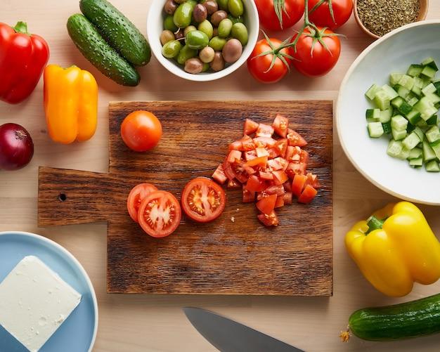 Schritt für schritt rezept für salat horiatiki, holzbrett zum schneiden von gemüse