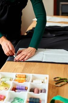 Schritt für schritt, weibliche schneiderin, die schnittmuster macht, reifer schneider, der mit schnittmuster im atelier, in der textilindustrie, im hobby, im arbeitsbereich arbeitet.
