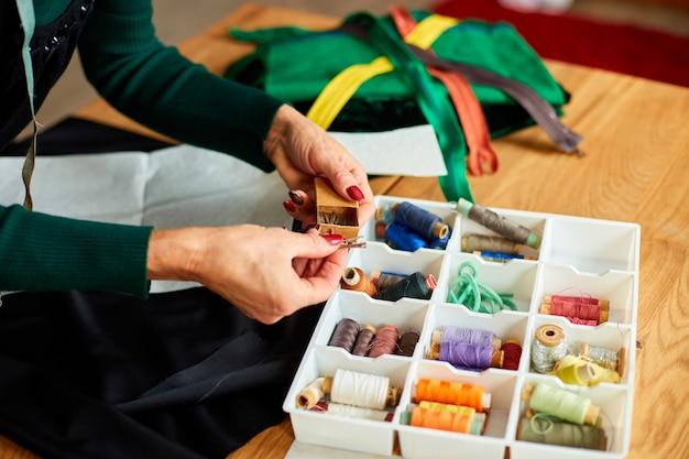 Schritt für schritt zieht die schneiderhand der frau den faden aus der schachtel. der reife schneider arbeitet im atelier, in der textilindustrie, im hobby und im arbeitsbereich.