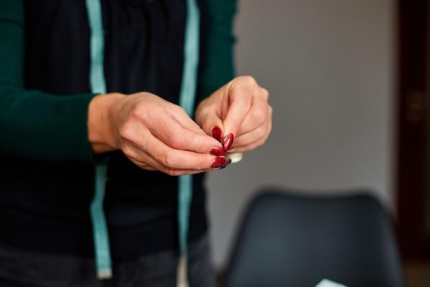 Schritt für schritt zieht die schneiderin den faden in die nadel, der reife schneider arbeitet mit dem nähen im atelier, in der textilindustrie, im hobby, im arbeitsbereich.