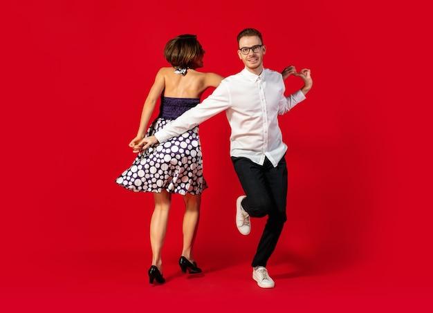 Schritt. old-school altmodisches junges paar tanzen auf rotem studiohintergrund isoliert. künstlermode, bewegungs- und aktionskonzept, jugendkultur, moderückkehr. junger stilvoller mann und frau.