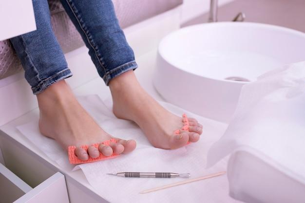 Schritt zum auftragen von gelpolitur in der pediküre. professionelle werkzeuge für die maniküre. beauty-spa-prozedur im salon
