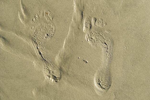 Schritte am strand im sand. schritte am korallensandstrand. fußabdrücke im sand.