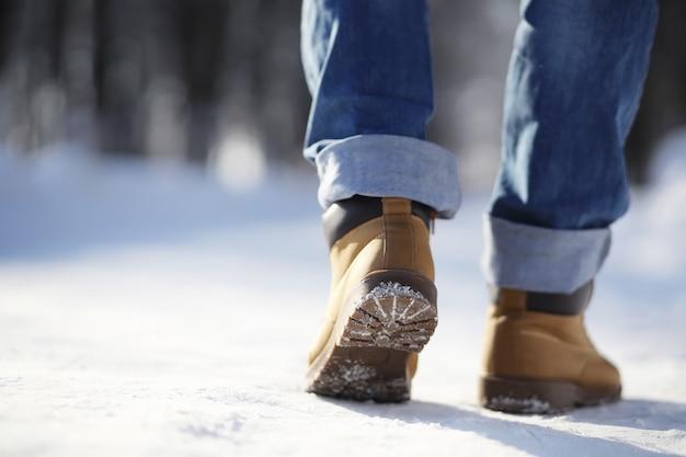Schritte auf dem schneebedeckten weg. ein mann geht im winter im park spazieren.