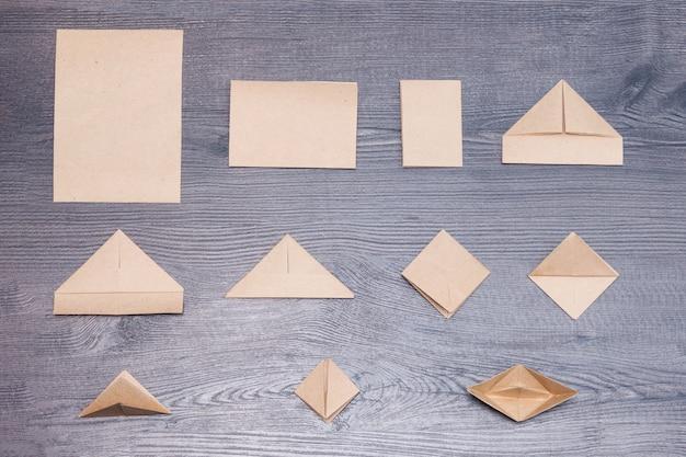 Schritte der herstellung des origami-papierboots auf hölzernem hintergrund.