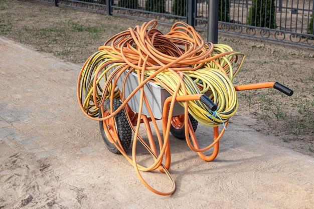 Schubkarre mit elektrokabeln und wasserschläuchen. vorbereitung auf die arbeit. bewegen von lasten auf der baustelle.