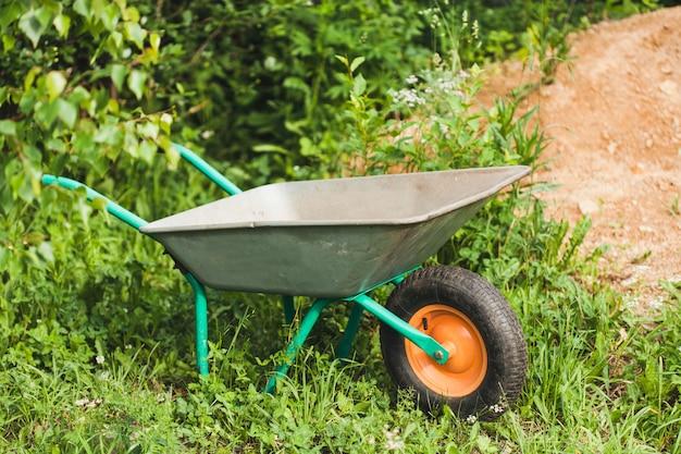 Schubkarre, wagen zum transport von land, material, gras und anderen dingen im garten, gartenarbeit, bau, feldarbeit, pflanzen, beeten