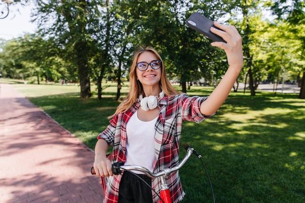 Schüchterne blonde frau in der brille, die telefon für selfie in guten sommertag verwendet. hübsches kaukasisches mädchen, das mit rotem fahrrad aufwirft.