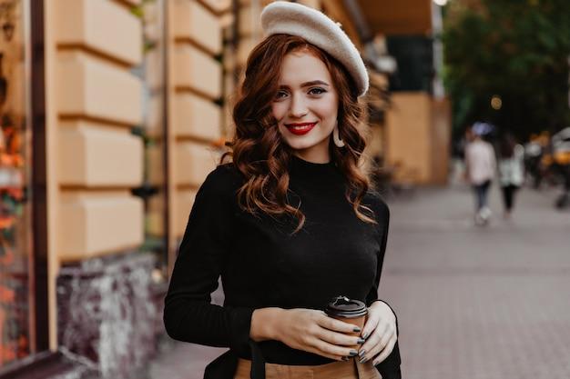 Schüchterne französische frau mit langen haaren, die draußen aufwerfen. entzückende rothaarige dame, die auf der straße mit tasse kaffee steht.