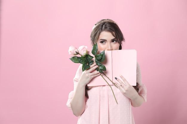 Schüchterne frau, die rosen hält und gesicht hinter buch versteckt