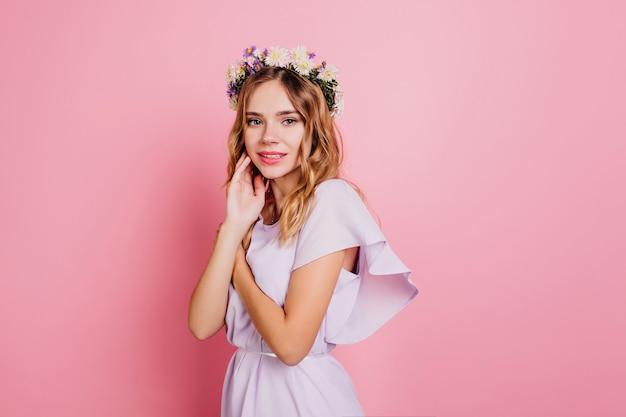 Schüchterne frau im romantischen sommeroutfit, das auf rosa wand aufwirft