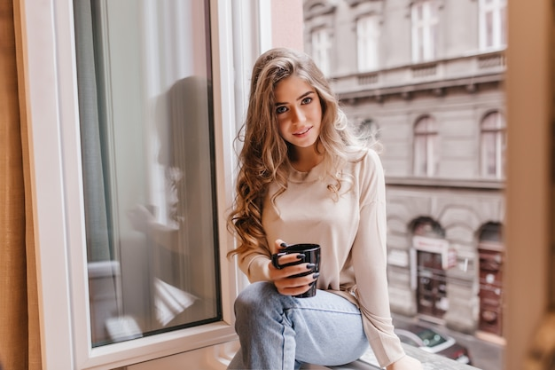 Schüchterne frau in jeans, die auf fensterbank sitzt und mit interesse aufwirft