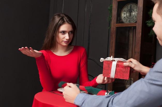 Schüchterne frau lehnt geschenk im restaurant ab