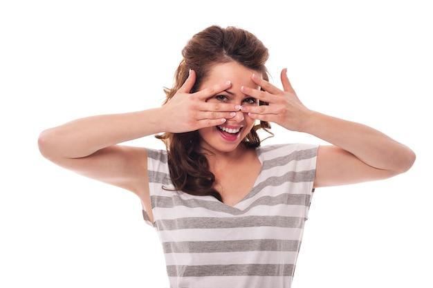 Schüchterne frau versteckt sich hinter den fingern