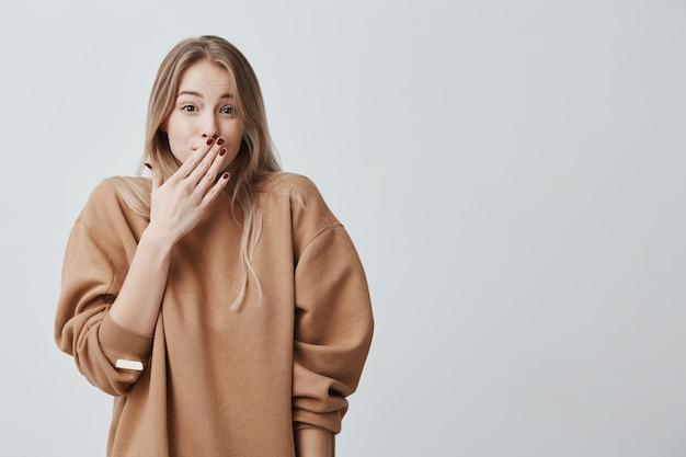 Schüchterne junge frau. nahaufnahmeporträtfrau mit blondem haar, das beschämt oder schüchtern aussieht, im vollen unglauben ist, durch nachrichten geschockt, gesicht hinter hand versteckt, isoliert.