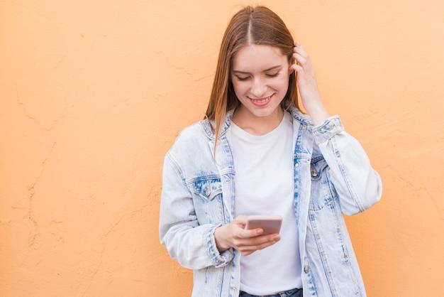 Schüchterne lächelnde frau, die mobiltelefon über beige strukturierter wand verwendet